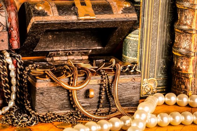 Schatkisten met goud. parels en gouden kettingen. vintage-stijl.