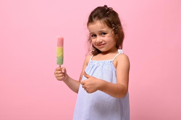 Schattig 4 jaar mooi babymeisje met gezonde veganistische ijslolly in de hand en duim opdagen, poseren op roze muur achtergrond, kopieer ruimte. zomerdessert, vrolijk zomers sfeerconcept