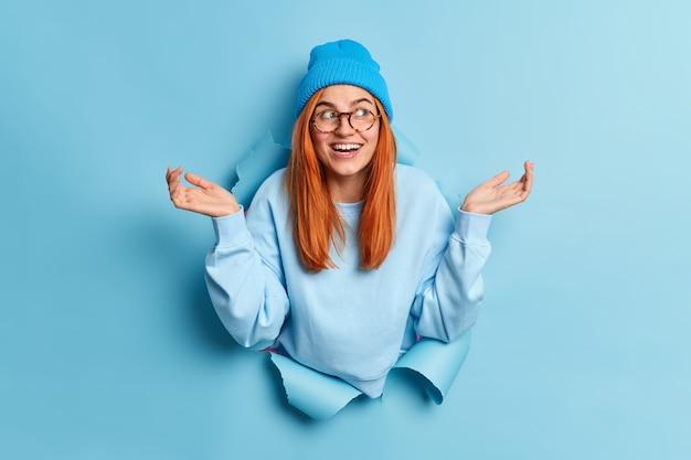 Schattig aarzelend roodharig europees meisje spreidt haar handpalmen en staat geen idee hoe ze zich moet gedragen, kijkt twijfelachtig ergens draagt een casual trui.