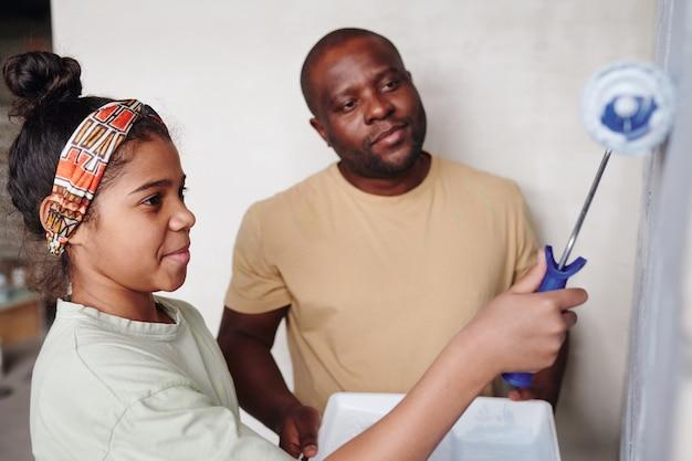 Schattig afrikaans meisje met verfroller die voor de bakstenen muur van de woonkamer staat terwijl ze het in witte kleur schildert tegen haar vader