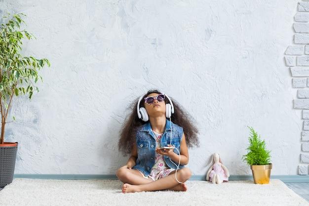 Schattig afro meisje thuis luisteren naar muziek