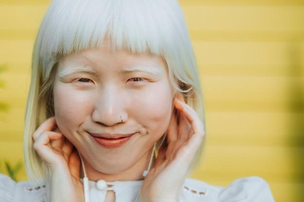 Schattig albino-meisje luistert naar haar favoriete muziek via oortelefoons