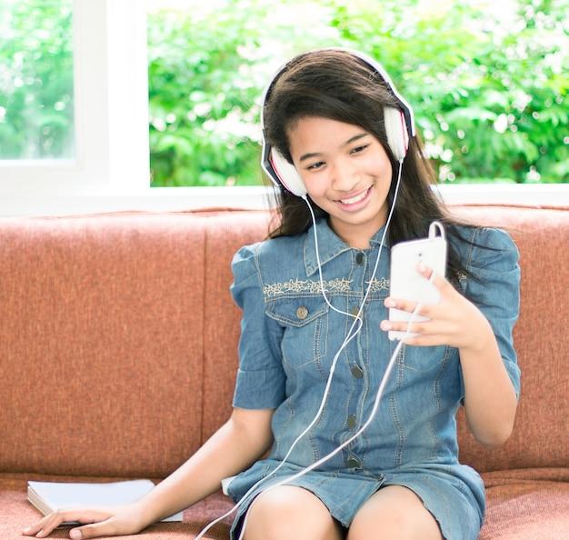 Schattig amerikaans meisje luisteren muziek spelen vanaf slimme telefoon