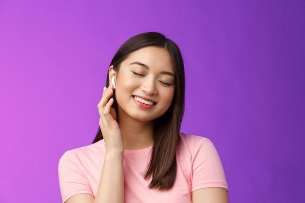 Schattig aziatisch meisje dat geniet van het luisteren van muziek, een draadloze hoofdtelefoon op, kantelt het hoofd, sluit de ogen, dromerige lachende tevredenheid, perfect geluid, maakt de oortelefoon luider, staat op een paarse achtergrond.