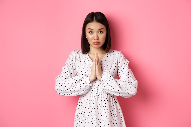 Schattig aziatisch meisje dat om hulp vraagt, om gunst smeekt en onschuldig naar de camera kijkt, smekend tegen roze achtergrond
