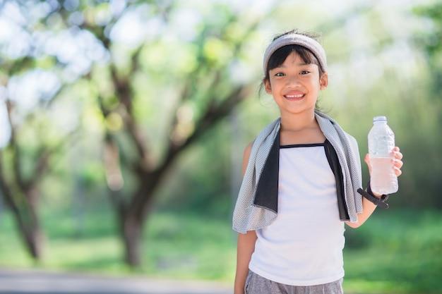 Schattig aziatisch meisje drinkt water uit een fles buiten met zonlicht
