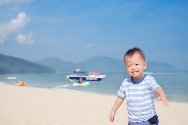 Schattig aziatisch peuterjongen dat in de zomervakantie op het tropische zandstrand loopt, kinderen spelen op zee at