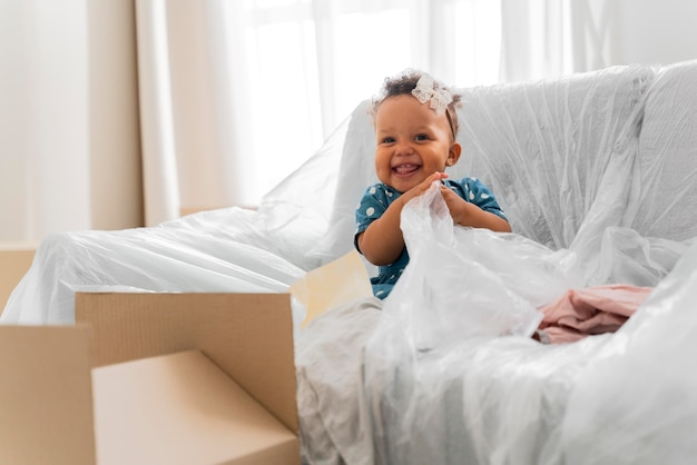 Schattig babymeisje dat in haar oude huis zit voordat ze gaat verhuizen