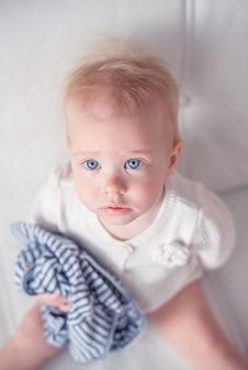Schattig babymeisje kijkt omhoog en houdt een gestreepte blouse op haar hand, geïsoleerd op een witte achtergrond