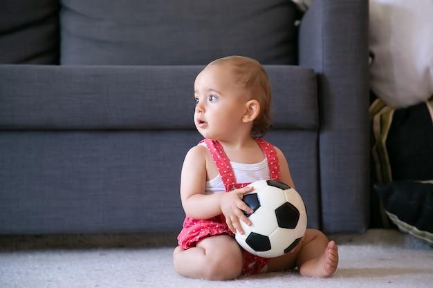 Schattig babymeisje met voetbal, zittend op een tapijt op blote voeten en wegkijken. schattige baby in rode tuinbroek korte broek spelen alleen thuis. vakantie-, weekend- en jeugdconcept