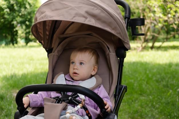 Schattig babymeisje van ongeveer 1 jaar oud zittend op koets, wandelwagen rondkijken op de achtergrond van groene bladeren, bomen. buiten wandelen met kind in park bij zonnig zomerweer. vrije tijd buitenshuis