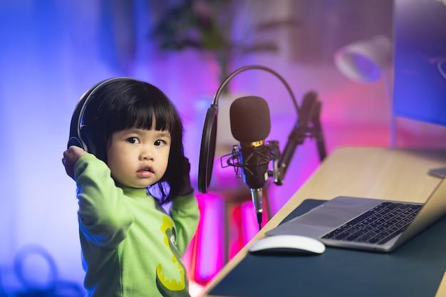 Schattig babymeisje zingt met hoofdtelefoon die nieuw nummer opneemt met microfoon in de thuisopnamestudio