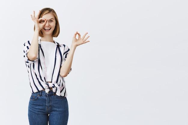 Schattig blond meisje kijkt door goed gebaar met geamuseerd geïntrigeerd gezicht