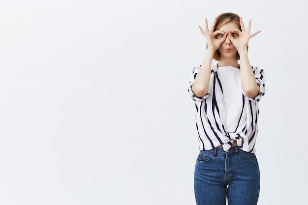 Schattig blond meisje kijkt door handbril met geamuseerd gezicht