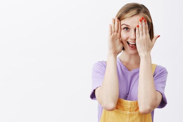Schattig blond meisje speelt kiekeboe, toont de helft van het gezicht en lacht geamuseerd