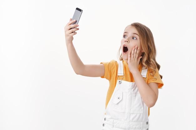Schattig charismatisch klein kaukasisch meisje, kind speelt met smartphone die grappige speelse grimas maakt, verleng arm houd mobiele telefoon die selfie neemt met verbaasde verbaasde emotie, witte muur