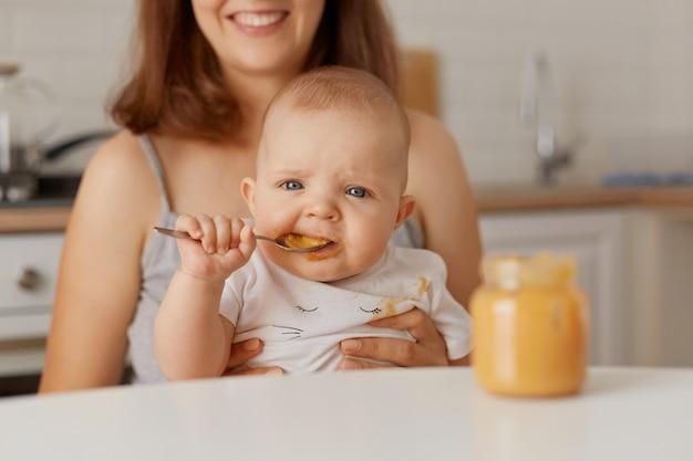 Schattig charmant babymeisje met een wit t-shirt houdt de lepel alleen vast, eet fruit of groentepuree uit een pot, aanvullende voeding, familie in de keuken.