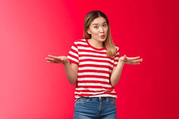 Schattig chill aziatisch blond college meisje praten vriendinnen bespreken gladde koele partij vouwen lippen schattig gespreide handen zijwaarts gebaren terloops, ontspannen vriendelijke pose, rode achtergrond.