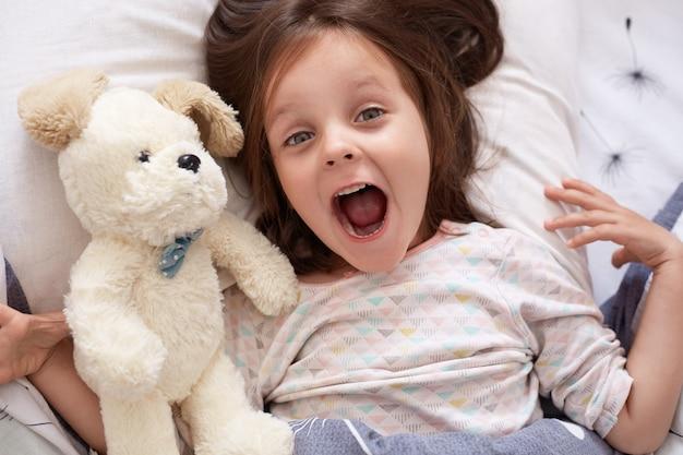 Schattig donkerharige babymeisje liggend in bed, opzoeken met verbaasde blik en geopende mond in de buurt van witte zachte hond