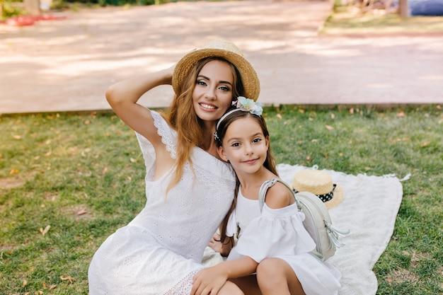 Schattig donkerogige meisje met lederen rugzak poseren op deken met stijlvolle jonge moeder draagt strooien hoed. outdoor portret van verfijnde vrouw in kanten jurk omhelst dochter met lint in haar.