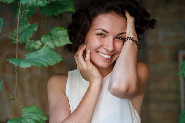 Schattig dromenmeisje met kort krullend haar. portret van glimlachende emotionele vrouw op stadsstraat in zonnige dag. gelukkige jonge dames gezicht buitenshuis