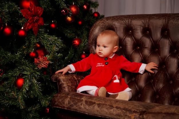 Schattig eenjarig meisje in het kostuum van de kerstman op de bank op de achtergrond van kerstboom versierd speelgoed. kind in decoraties met geschenkdozen. concept van gezellig huis gelukkig nieuwjaar viering. ruimte kopiëren