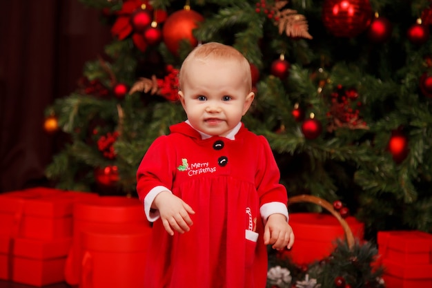 Schattig eenjarig meisje in santa claus kostuum op kerstboom versierd met speelgoed. kind in kerstversiering