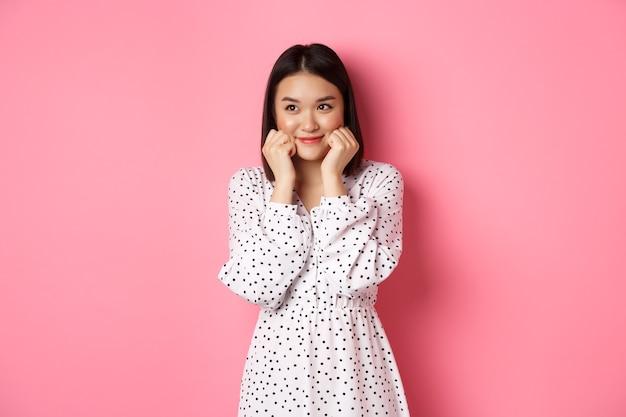 Schattig en verlegen aziatisch meisje dat bloost, wangen aanraakt en links naar de kopieerruimte kijkt, dom, staande tegen een roze achtergrond
