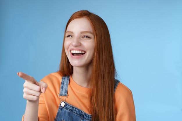 Schattig gefascineerd jonge aantrekkelijke tedere roodharige geamuseerd meisje plezier wijzend kijken links verbaasd lachen plezier zien grappige advertentie grinniken vrolijk blauwe achtergrond