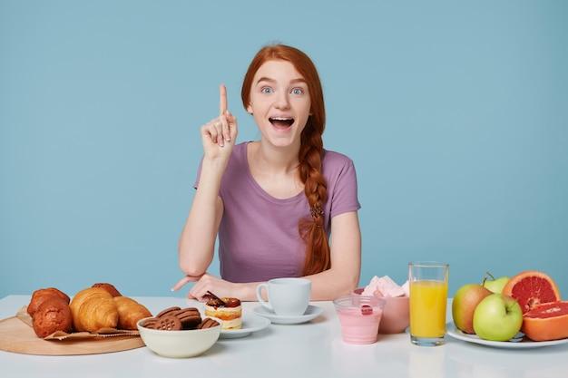 Schattig geïnspireerd opgewonden roodharig meisje zittend aan tafel tijdens het ontbijt