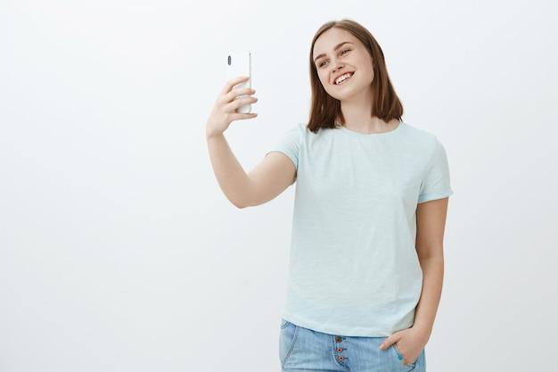 Schattig, gelukkig en zelfverzekerd meisje dat met moeder praat via videoboodschappen terwijl ze in het buitenland studeert terwijl ze het hoofd van de smartphone kantelt en glimlacht naar het scherm van het apparaat, selfie neemt over witte muur