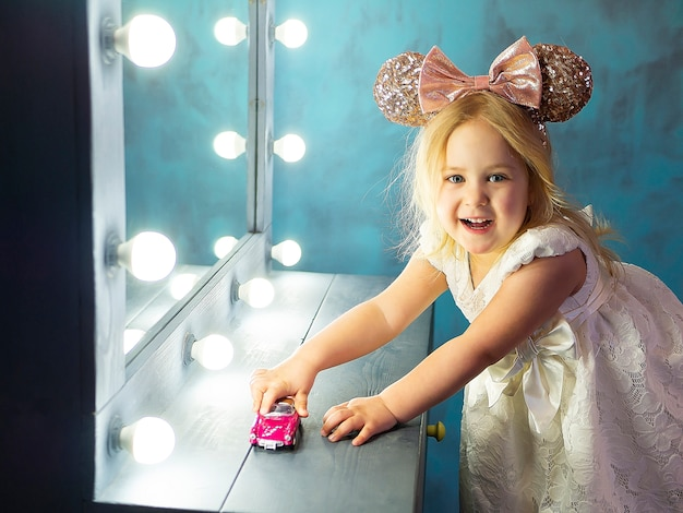 Schattig gelukkig klein babymeisje spelen met speelgoed. modern kinderdagverblijfbinnenland, vroeg het leren concept.