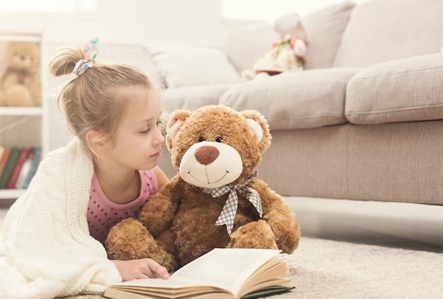 Schattig gelukkig klein casual meisje omhelst teddybeer en leesboek, gewikkeld in een witte deken. mooi kind thuis, liggend op de vloer in de buurt van de bank met haar favoriete speeltje, kopieer ruimte
