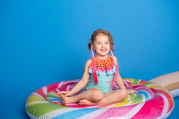 Schattig gelukkig klein meisje in zwempak glimlachend zittend op kleurrijke opblaasbare matras.