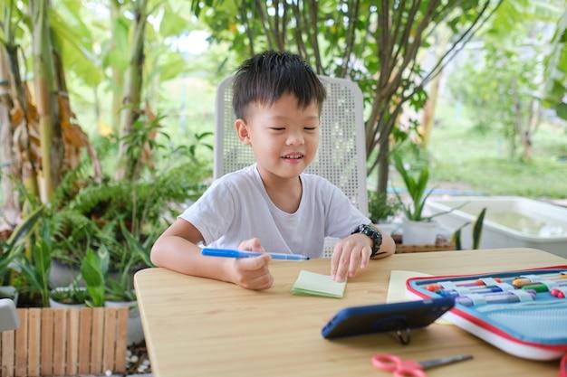 Schattig gelukkig lachend aziatisch kleuterkind geniet van thuis knutselen in de natuur, kleine jongen die smartphone studeert tijdens zijn online les, kinderkunstproject, thuisonderwijsproject