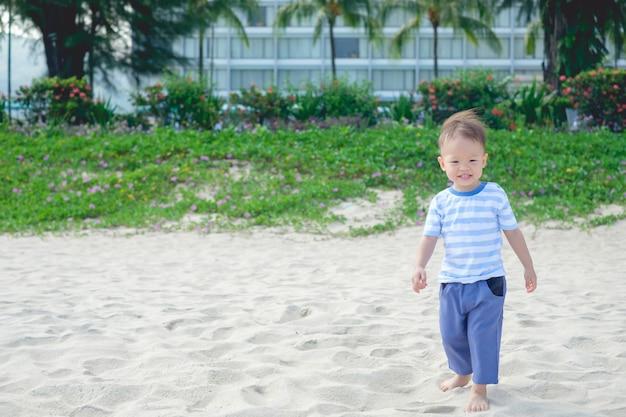 Schattig, gelukkig lachend, klein aziatisch peuterjongen dat blootsvoets op het tropische zandstrand staat