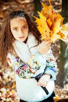 Schattig gelukkig meisje de gevallen bladeren overgeven, spelen in het herfstpark