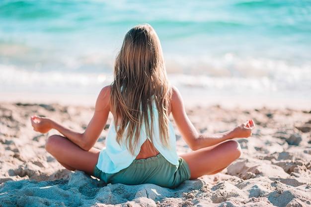 Schattig gelukkig meisje op strandvakantie in meditatie