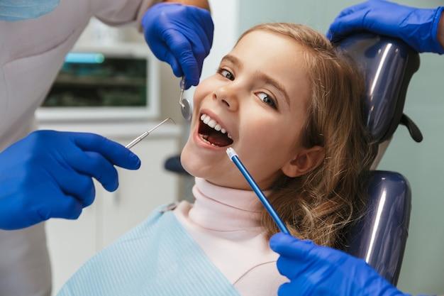 Schattig gelukkig mooi kind meisje zit in medisch tandarts centrum camera kijken.