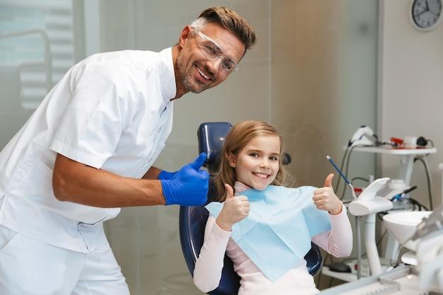 Schattig gelukkig mooi kind meisje zit in medisch tandarts centrum duimen opdagen