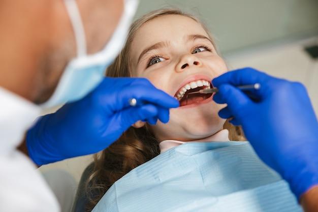Schattig gelukkig mooi kind meisje zit in medisch tandarts centrum