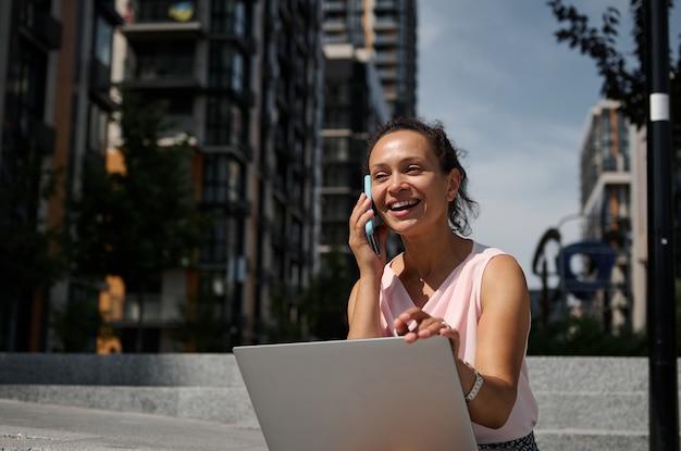 Schattig gemengd ras afro-amerikaanse vrouw praten op mobiele telefoon, zittend op de trap met een laptop op de stedelijke hoge gebouwen achtergrond. zakenvrouw tijdens de lunchpauze