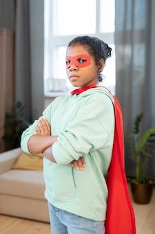 Schattig gemengd ras meisje in kostuum van superheld die de armen op de borst kruist terwijl ze voor de camera staat tegen een fauteuil en een groot raam