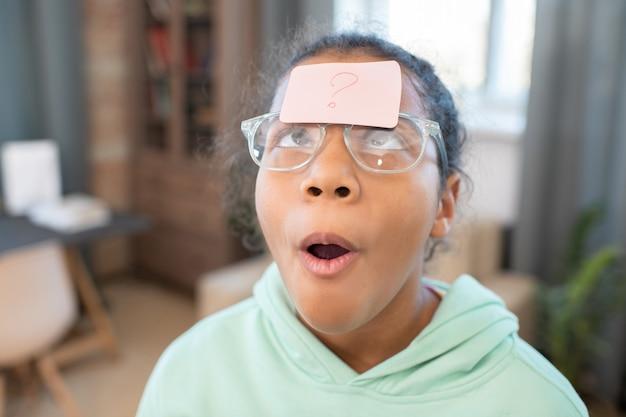 Schattig gemengd ras meisje in vrijetijdskleding en bril kijken naar briefpapier met vraagteken op haar voorhoofd tegen thuisomgeving