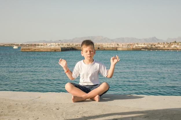 Schattig gezond gelukkig lachend klein peuter jongenskind met gesloten ogen beoefent yoga buiten mediteren op zee