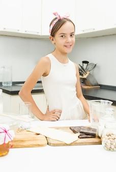Schattig glimlachend meisje leunend op een houten kookbord op de keuken