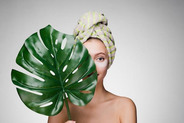 Schattig glimlachend meisje met een handdoek op haar hoofd met een groen blad, day spa, onder de ogen witte vlekken