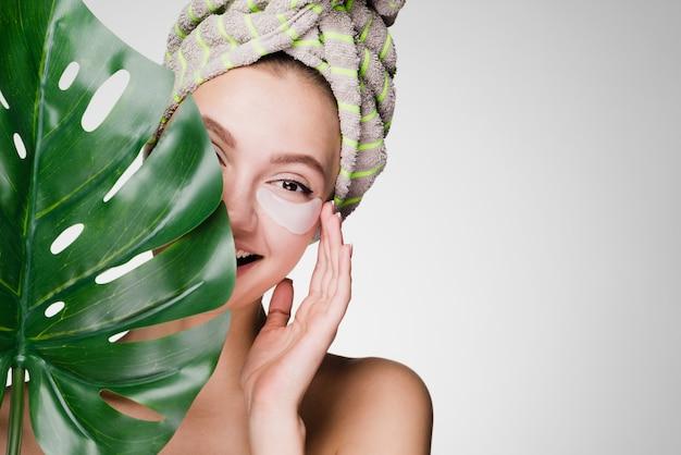 Schattig glimlachend meisje met een handdoek op haar hoofd met een groen blad, genietend van een spa, onder de ooglapjes