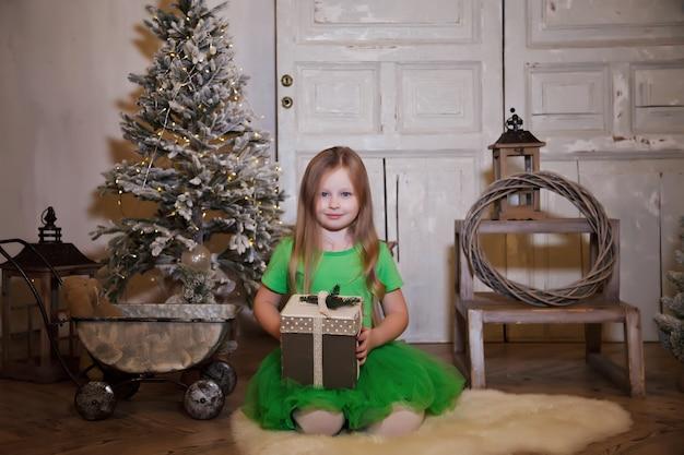 Schattig glimlachend zesjarig meisje met kerstcadeau over kerstboom