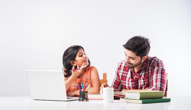 Schattig indiaas meisje met vader die thuis studeert of huiswerk maakt met laptop en boeken - online scholingsconcept